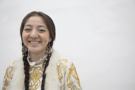 Portrait of young smiling woman with braids in traditional clothing from Kazakhstan, studio shot