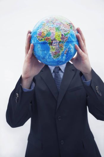 Businessman in a suit holding up a globe in front of his face, obscured face, studio shot