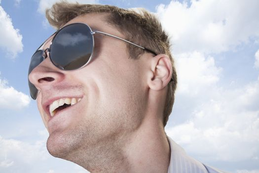 Portrait of young businessman in sunglasses smiling, close-up on face