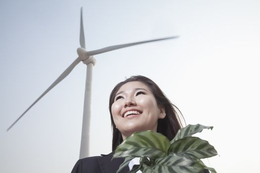 Portrait of smiling young businesswoman standing by a wind turbine and holding a plant