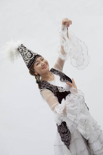 Portrait of young smiling woman dancing in traditional clothing from Kazakhstan, studio shot