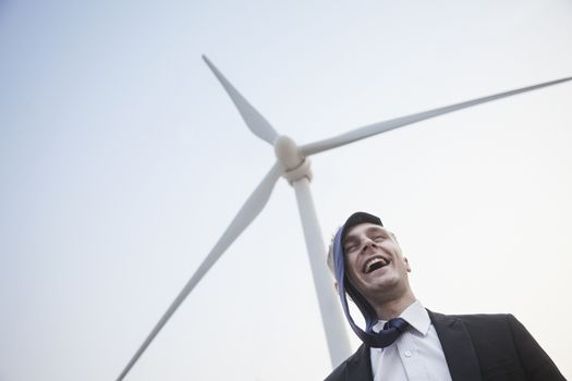 Young smiling businessman standing beside a wind turbine, tie is on his head