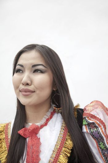 Portrait of young smiling woman in traditional clothing, studio shot
