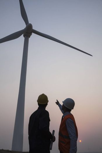 Two young male engineers standing beside a wind turbine at sunset, pointing up