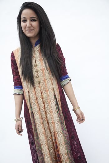 Portrait of smiling young woman wearing traditional clothing from Pakistan, studio shot