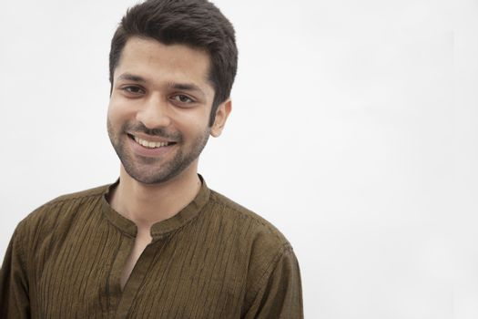 Portrait of smiling young man wearing traditional clothing from Pakistan, studio shot