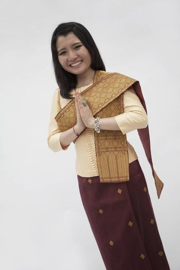 Portrait of smiling young woman with hands clasped together in traditional clothing from Laos, studio shot