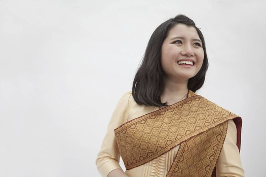 Portrait of smiling young woman in traditional clothing from Laos, studio shot