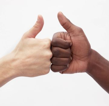 Two young men giving each other the thumbs up sign, close-up, studio shot