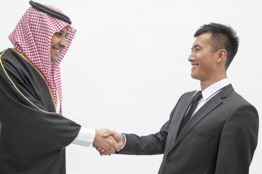 Smiling businessman and young man in traditional Arab clothing shaking hands, studio shot