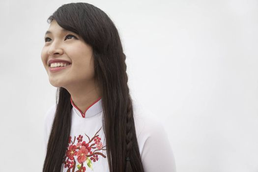 Portrait of smiling young woman with long hair wearing a traditional dress from Vietnam, studio shot