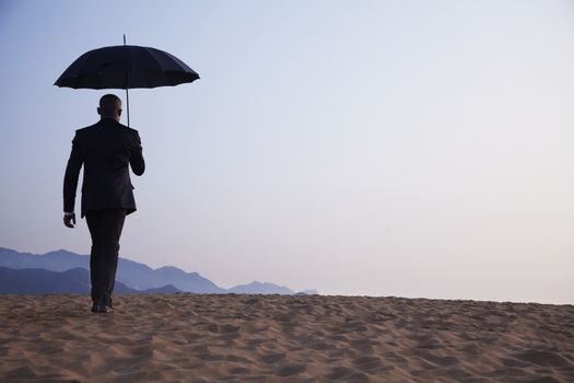 Businessman holding an umbrella and walking away in the middle of the desert