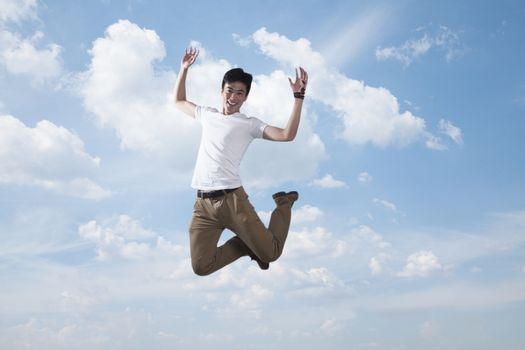 Young smiling man jumping in mid-air, sky and cloud background