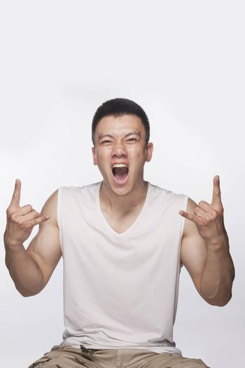 Excited man making hand sign with mouth open, studio shot