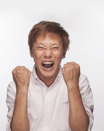 Excited man with fists raised and mouth open, studio shot
