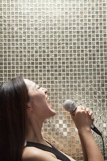 Side view of young woman singing into a microphone at karaoke, shiny background