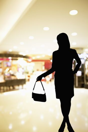 Silhouette of woman standing in a shopping mall ad holding a purse