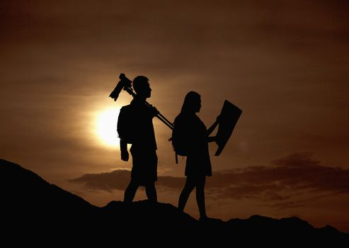 Silhouette of two people hiking and carrying camera and a map in nature at sunset