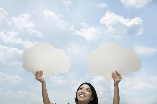 Young woman holding two cut out paper clouds against a blue sky with clouds