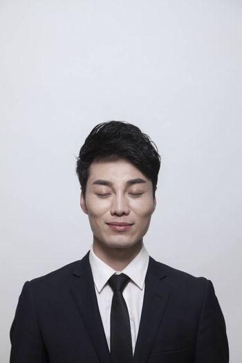 Relaxed young businessman with eyes closed, studio shot