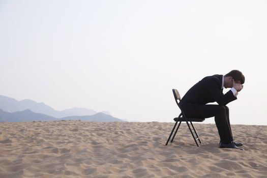 Businessman sitting with his head in his hands in the middle of the desert