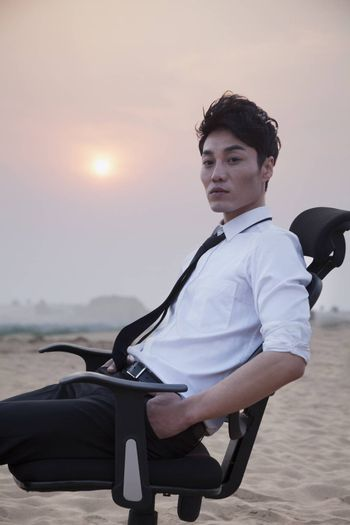 Businessman sitting on a chair and looking at camera in the middle of the desert
