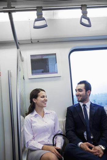Two young business people sitting and chatting on the subway