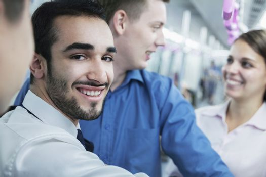 Portrait of young smiling businessman standing on the subway, looking at camera