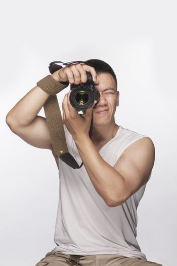 Man holding a camera and taking a photograph, studio shot