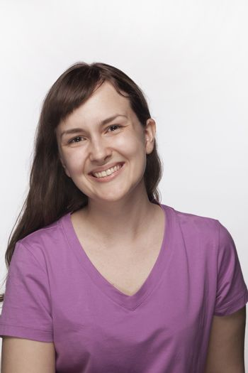 Portrait of smiling young woman in purple t-shirt, studio shot