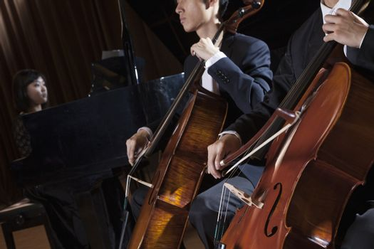 Two cellists playing the cello during a performance