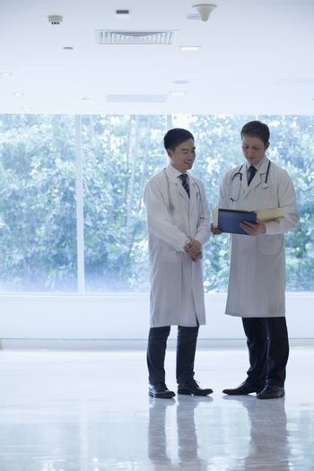 Two doctors standing, looking down, and consulting over medical record in the hospital