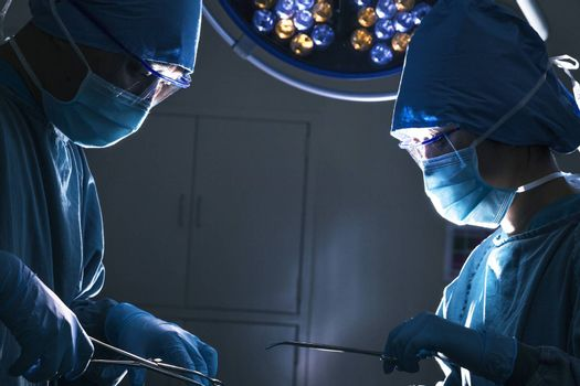 Two surgeons looking down and working at the operating table, dark operating room
