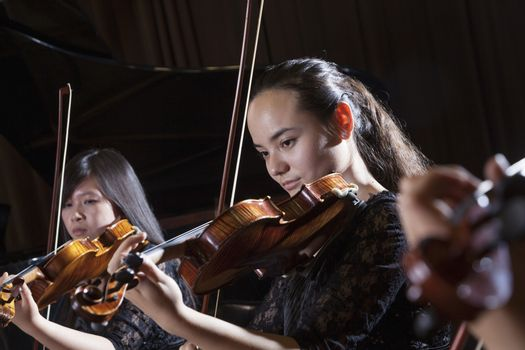 Violinists playing during a performance, head and shoulders