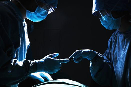 Two surgeons working and passing surgical equipment in the operating room, dark