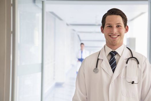 Portrait of young doctor in lab coat in the hospital, looking at camera