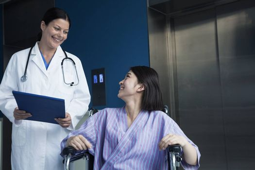 Young smiling female patient sitting in a wheelchair, looking up at the doctor standing beside her