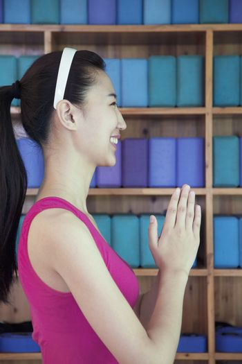 Portrait of young women doing yoga with hands clasped together, side view