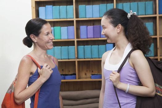 Two friends meeting at the yoga studio, holding bags