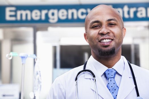 Portrait of smiling doctor outside of the hospital, emergency room sign in the background