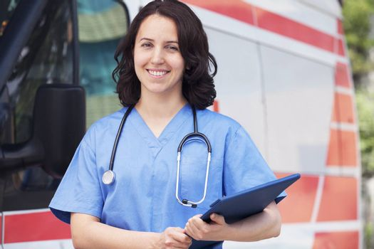 Portrait of smiling female paramedic in front of am ambulance