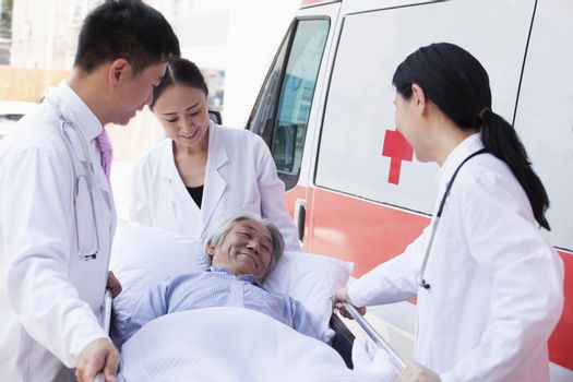 Three doctors wheeling in a elderly patient on a stretcher in front of an ambulance