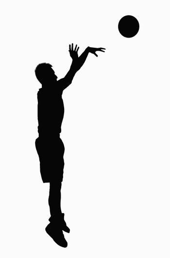 Silhouette of basketball player jumping.