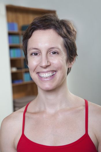 Portrait of smiling woman in a yoga studio, head and shoulders