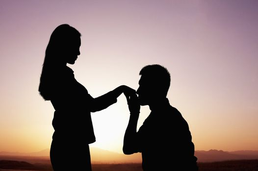 Silhouette of boyfriend kneeling and kissing his girlfriends hand at sunset