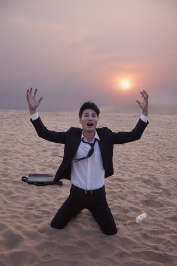 Frustrated businessman with arms outstretched kneeling in the desert at sunset