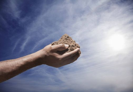 Hands holding a pile of soil with sun and sky in the background