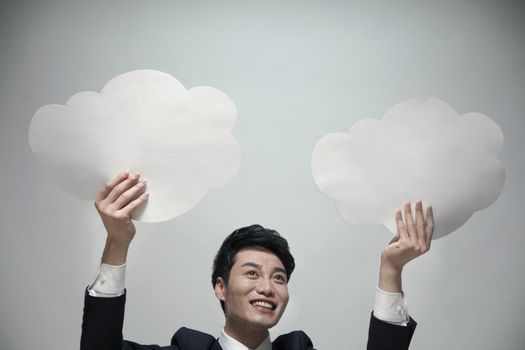 Smiling businessman holding two paper clouds, studio shot