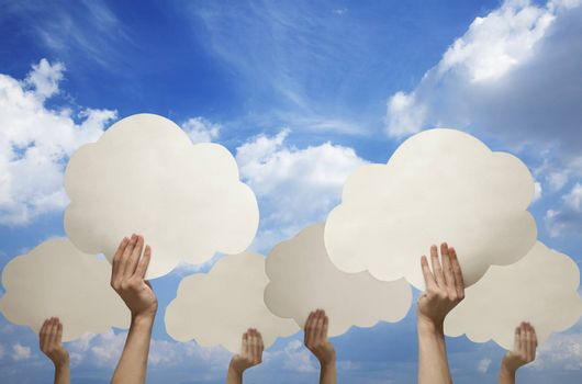 Multiple hands holding cut out paper clouds against a blue sky with clouds