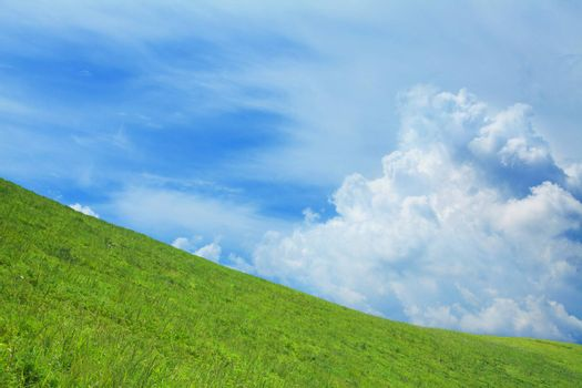 Lush, green hill with blue sky and clouds.